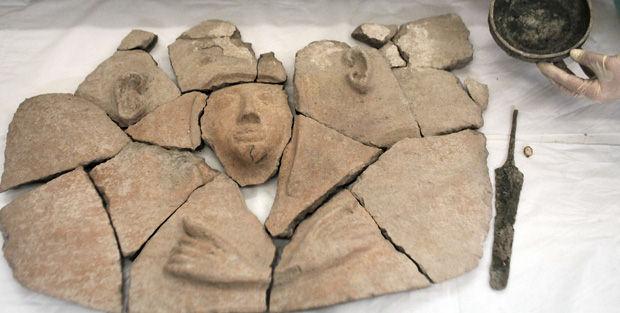 Objetos encontrados dentro del sarcófago: una daga, una copa y varias piezas martilladas, todas de bronce.