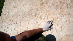 Arqueologo trabajando en el fragmento de piedra